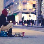 A homeless woman sitting on the sidewalk.