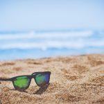 A pair of sunglasses on the beach.