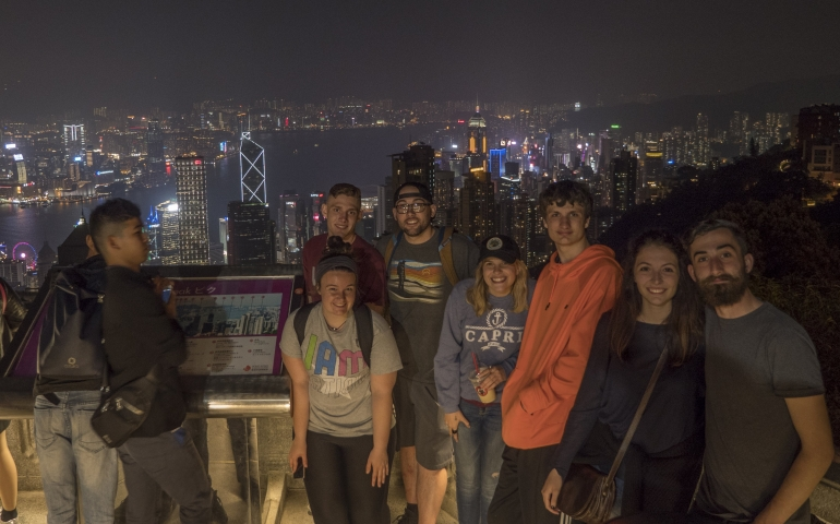 students standing in front of a city