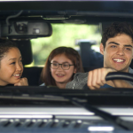 three teens riding in a car together smiling