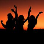 Shadowed people dancing on a summer night