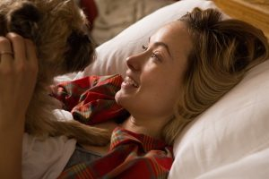 A woman and a dog in bed