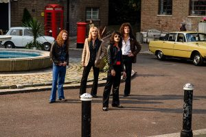 The four actors playing Queen outside on a street
