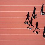 Runners on a track showing their shadows