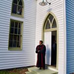 Female pastor standing in front of the church doors