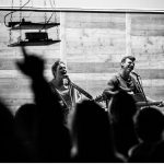 Two people singing while others put their hands up in worship