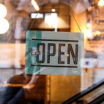 """A sign on a store front that reads """"Yes, we are open""""."""