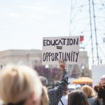"""Man holding a sign which reads """"education = opportunity""""."""