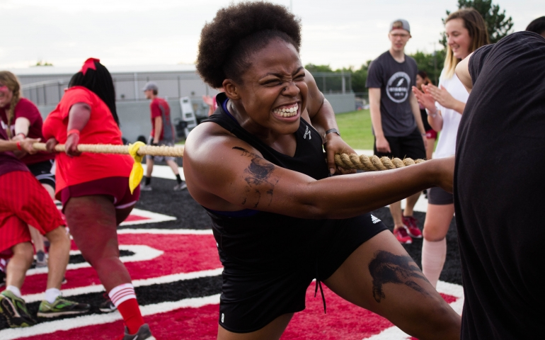 A student grimacing as she pulls on a rope for tug-of-war