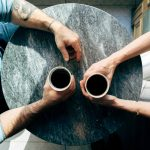 Man and woman conversing over coffee at a table