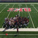 Crimson Storm football team huddled on the football field