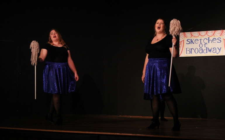 Two women singing with mops