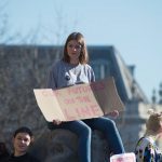 """Girl with a sign that says """"The Future's On the Line"""""""