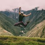 Woman jumping on a hike in the mountains