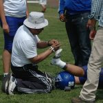 Trainer helping football player