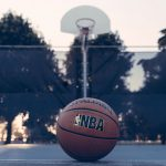 NBA basketball in front of a basketball hoop outside